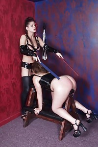 Splendid butted slave angel rests her belly to a couch while a kinky babe spanked her sexy butt